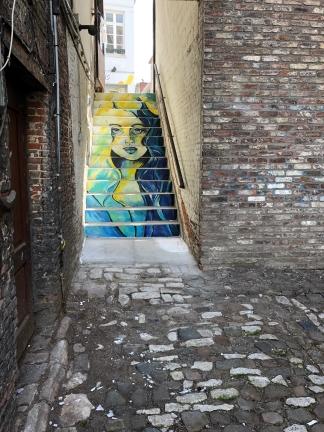 Muurschildering Mechelen: Vrouw op trap Onze-Lieve-Vrouwestraat